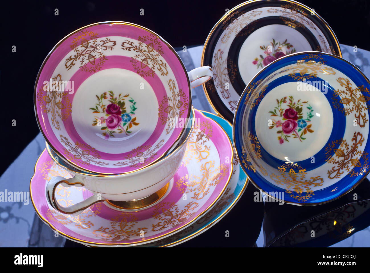 Beautiful colourful best china Cups & Saucers displayed on glass table ready for Sunday afternoon tea with friends - Stock Image