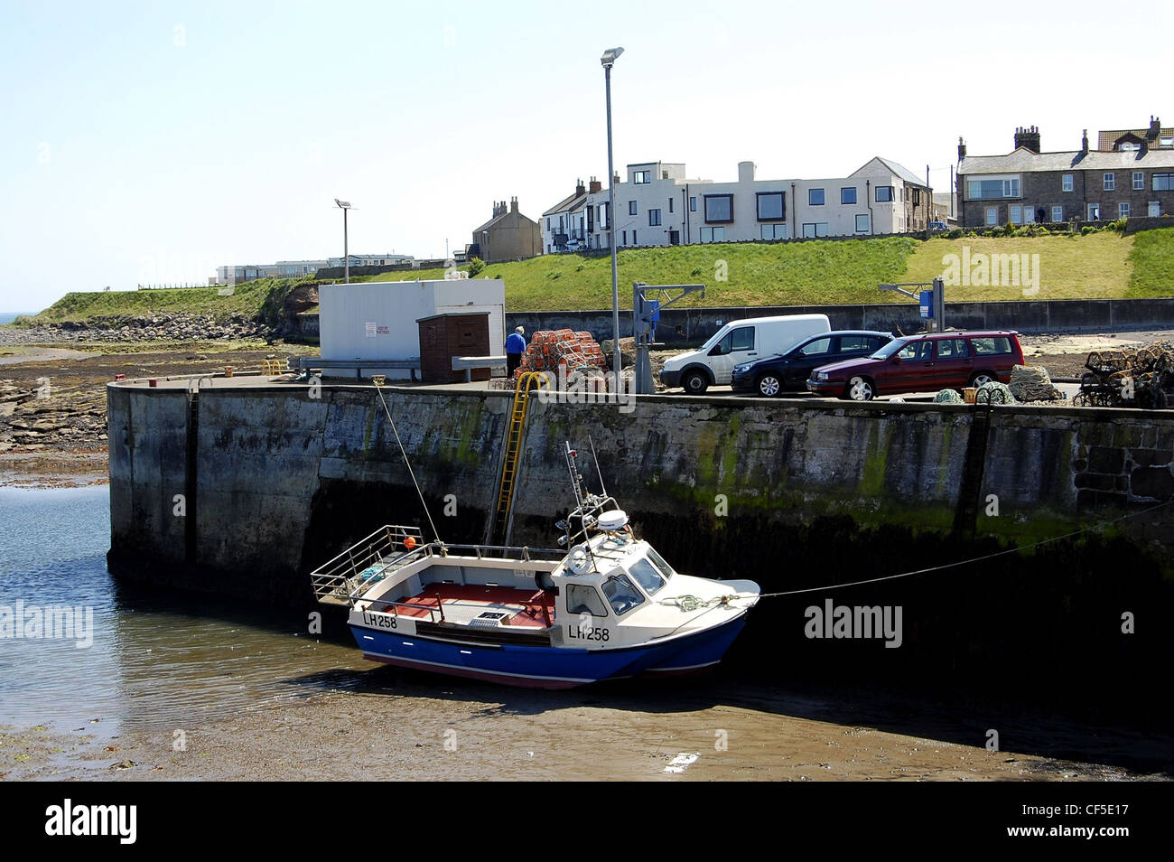 Seahouses harbour with boat resting on the bottom of the harbour at low tide - Stock Image
