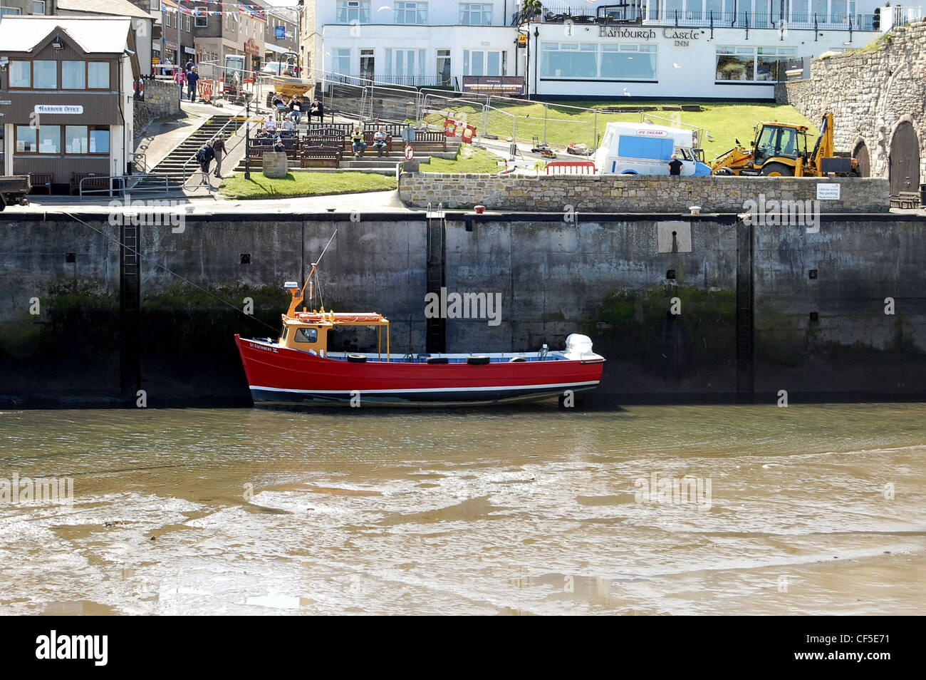 Seahouse harbour at low tide with boat resting on the muddy seabed with harbour master's office and seated people - Stock Image