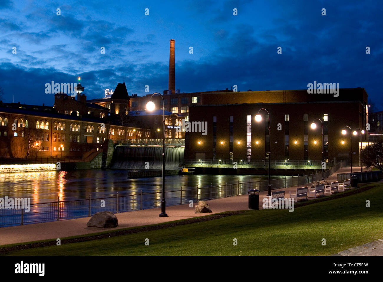 Tammerkoski river, old factory buildings around it and blue sky at Tampere Finland. - Stock Image