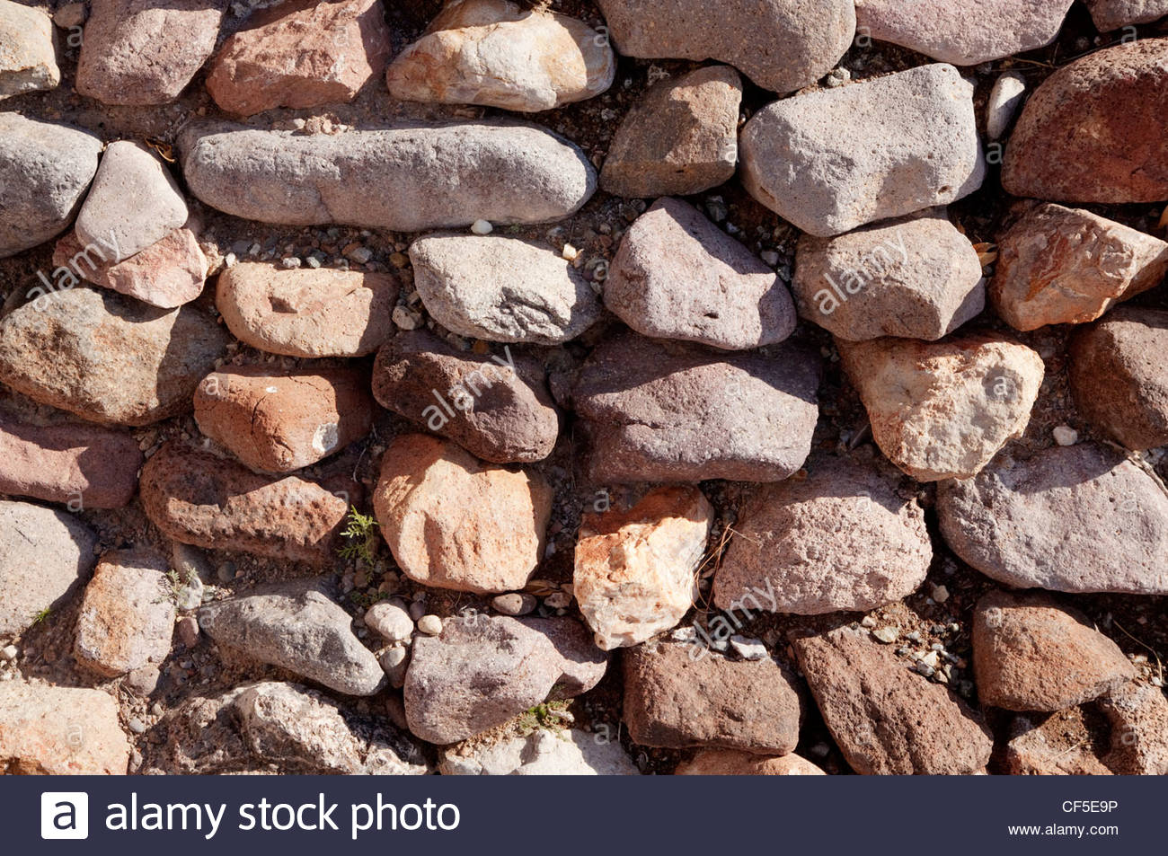 Dry Rock Wall rounded stones texture background - Stock Image
