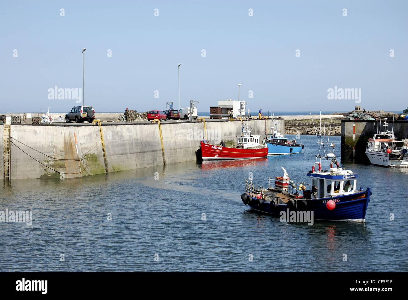 Seahouses Harbour, Northumberland with moored boats and one moving - Stock Image