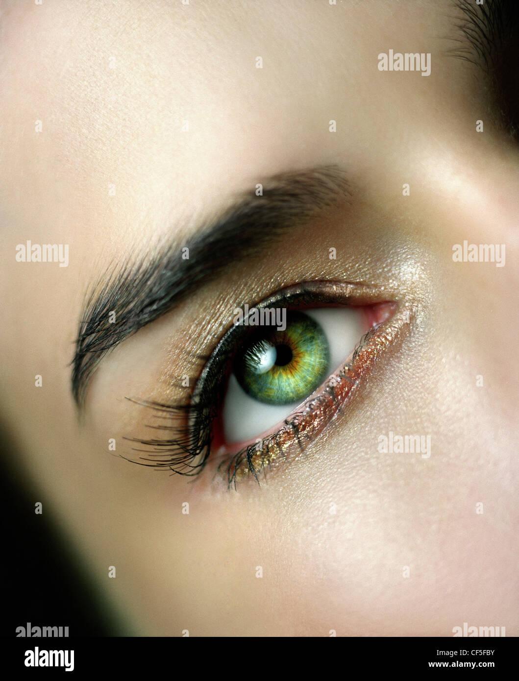 Female wearing gold shimmer eyeshadow, black liquid eyeliner and false eyelashes - Stock Image