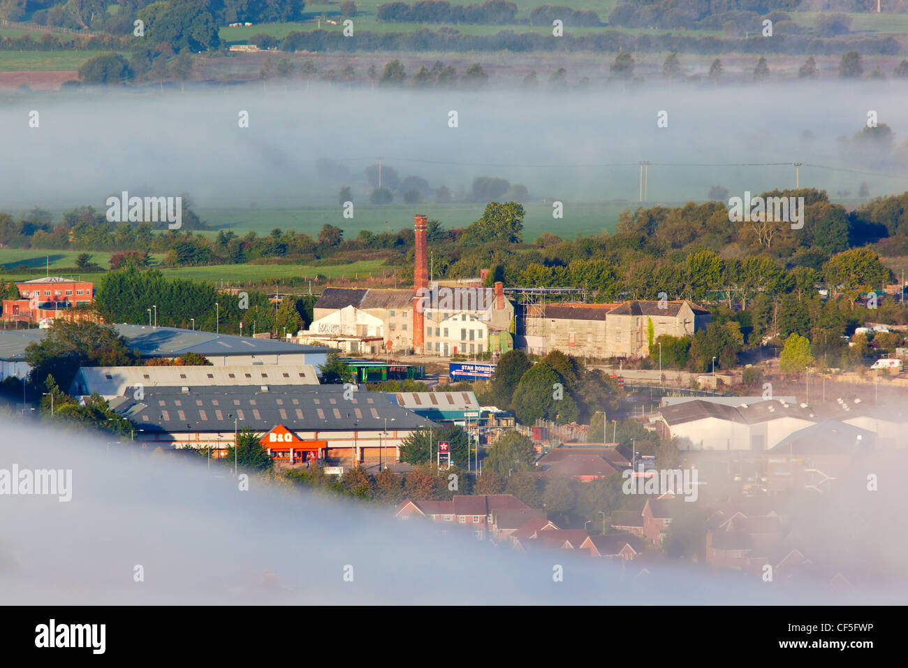 View from Glastonbury Tor over mist surrounding retail outlets and old factories near Glastonbury town centre. - Stock Image