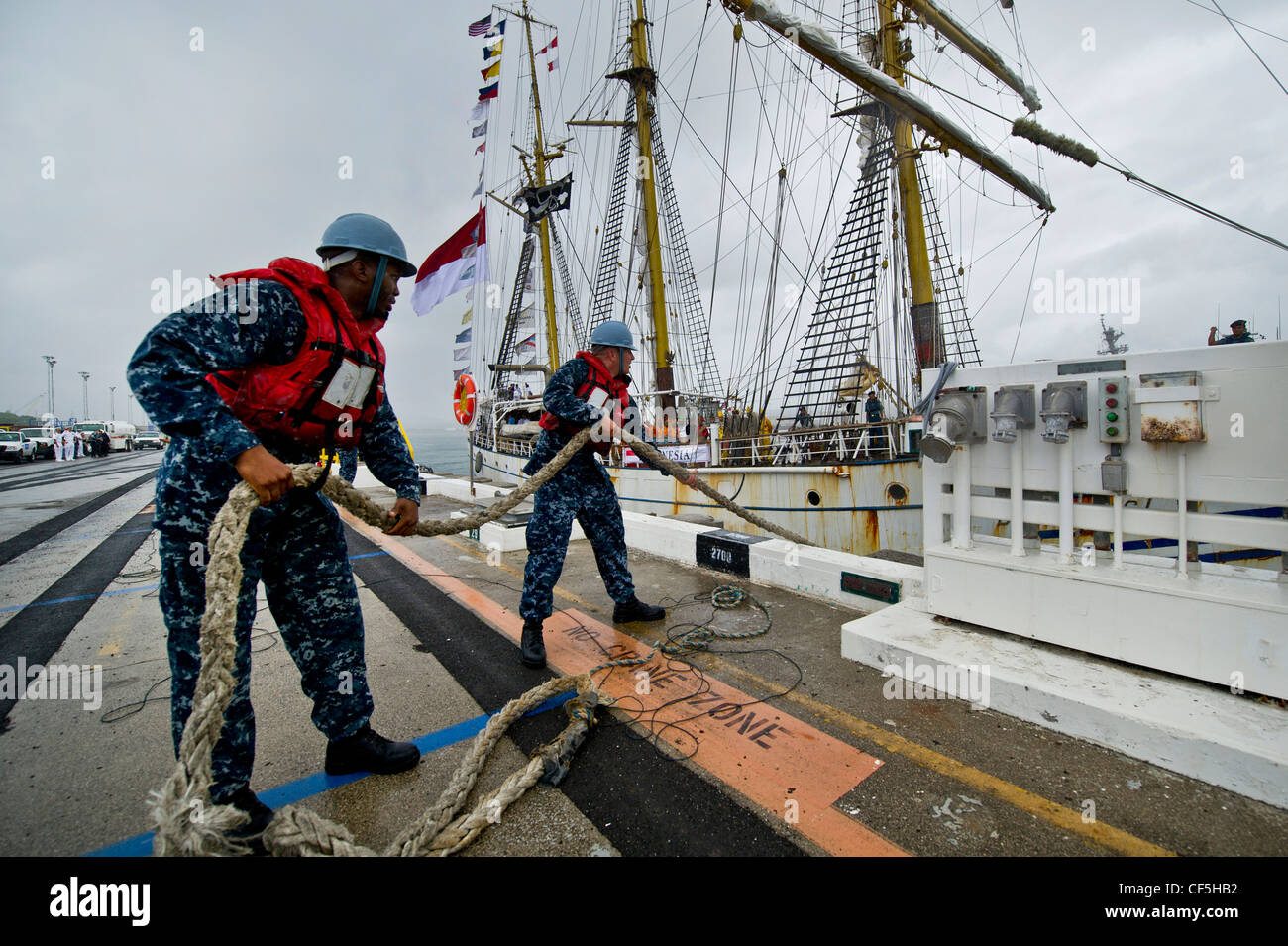 U.S. Navy Boatswain Mates help tie off the lines of the Indonesian Navy tall ship, KRI Dewaruci as it arrived at - Stock Image