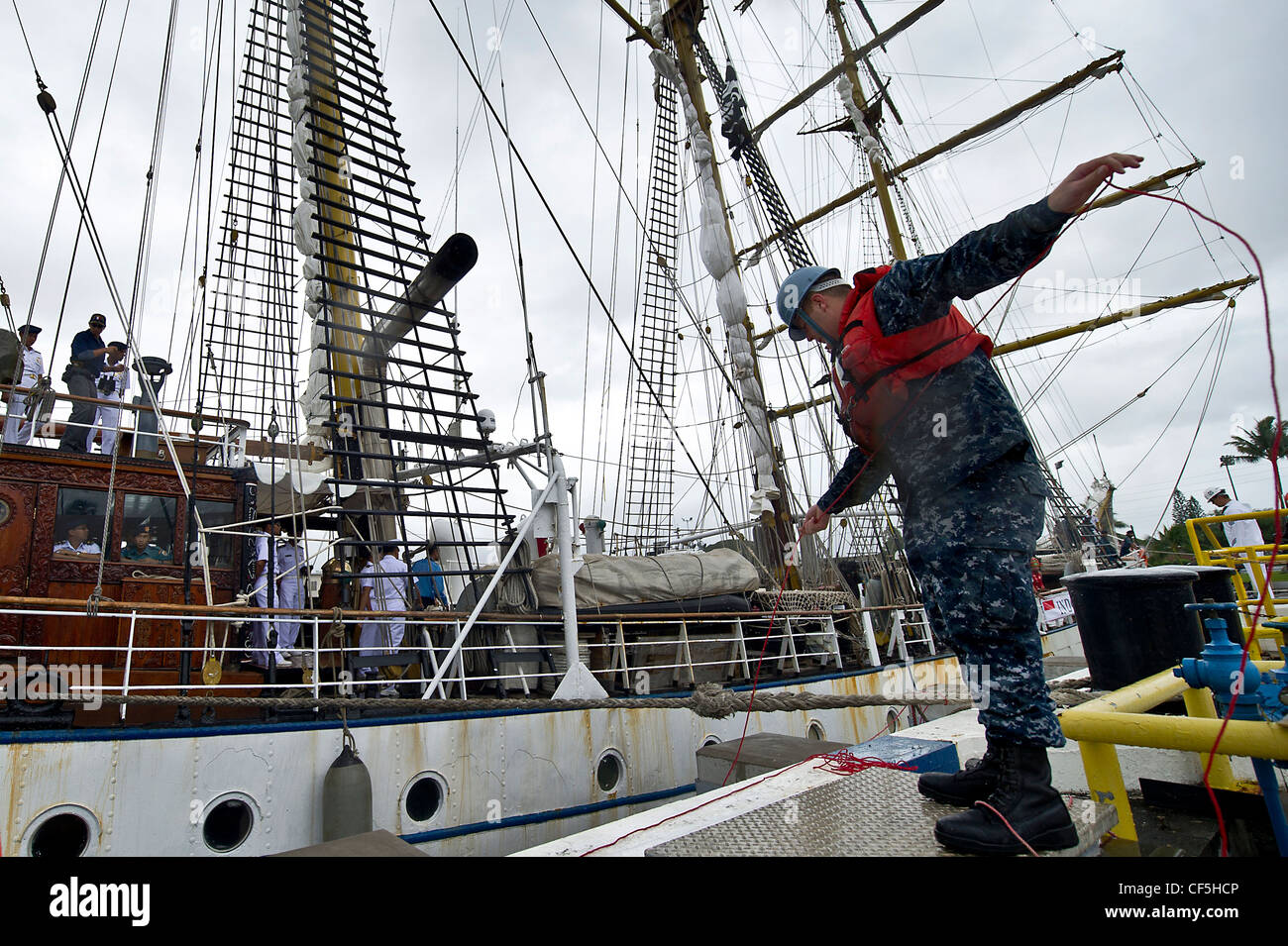 U.S. Navy Petty Officer 3rd Class Christopher Maddock helps tie off the lines of the Indonesian Navy tall ship, - Stock Image