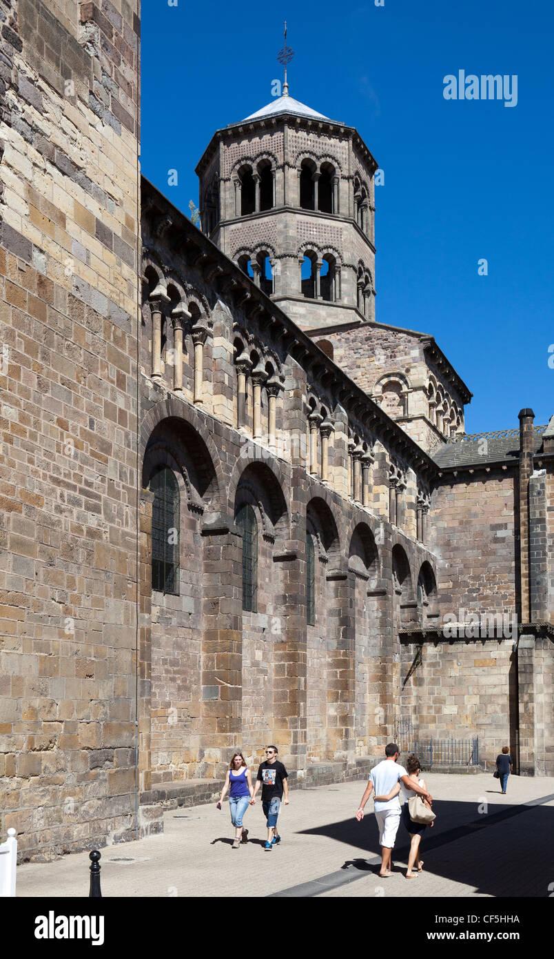 People walking past the Abbatiale Romane Saint-Austremoine decorated church, Issoire, Puy-de-Dome, Auvergne, France - Stock Image