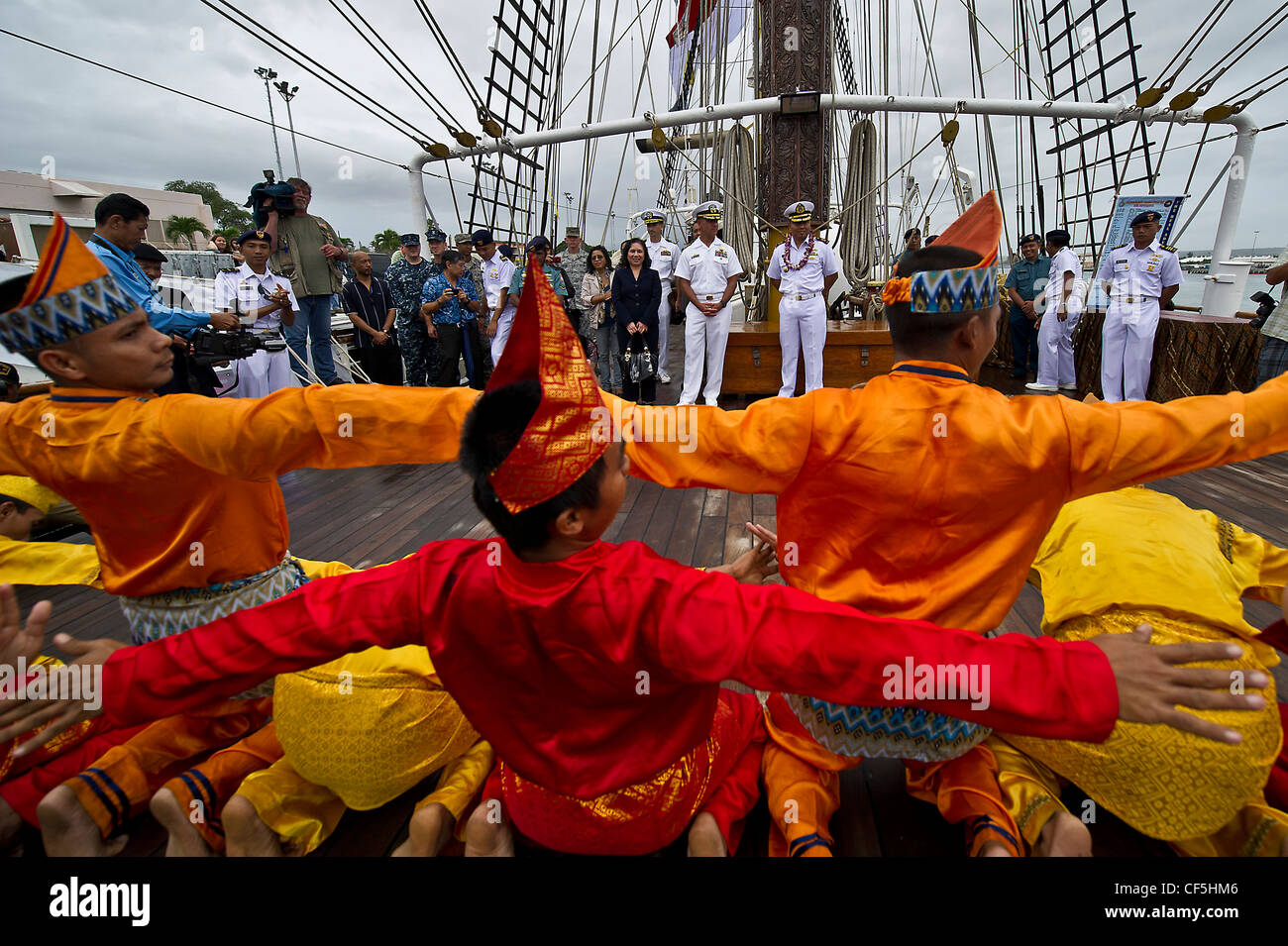 Indonesian sailors perform a traditional dance to welcome U.S. Military personnel aboard the Indonesian Navy tall - Stock Image