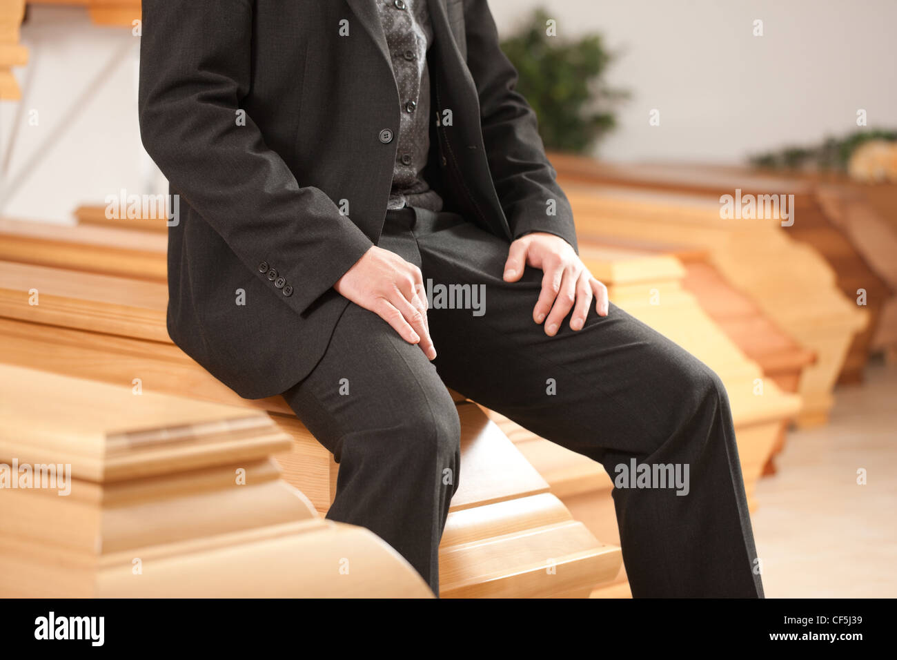 Undertaker in his store with a display of coffins Stock Photo