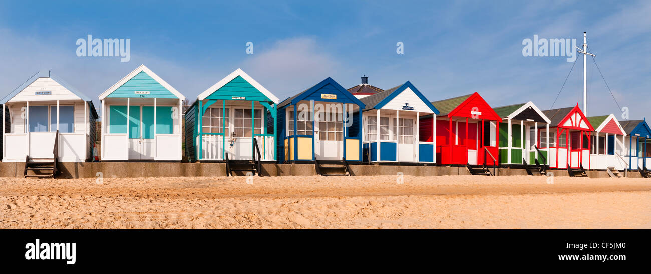 Colourful beach huts along the seafront in Southwold. - Stock Image
