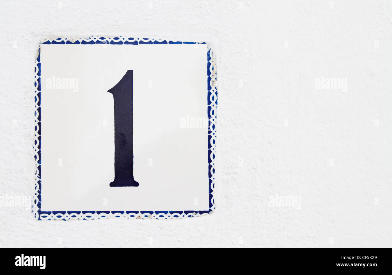 Spanish house number one wall tile on the outside of a white house - Stock Image