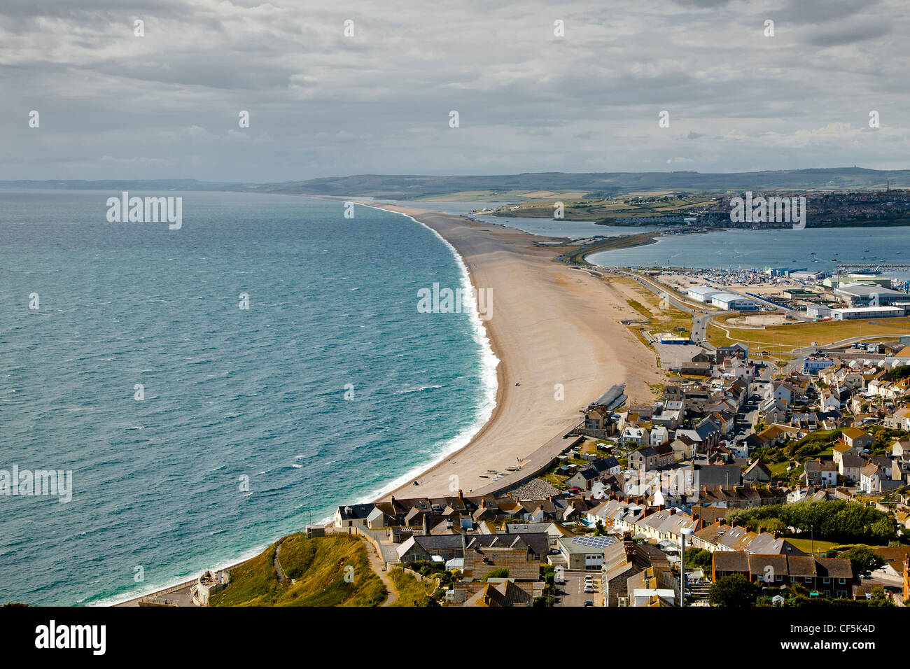 View over the village of Chesil along Chesil Beach, a 29 km long shingle beach on the Jurassic Coast of Dorset. - Stock Image