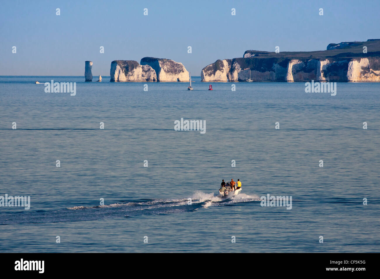 People aboard a speed boat heading towards Old Harry Rocks, two chalk sea stacks on the Isle of Purbeck. Stock Photo