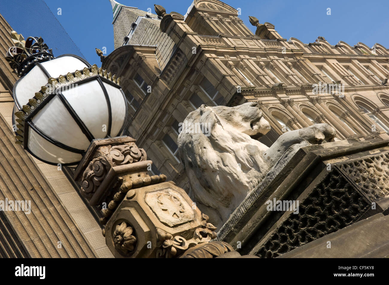 A carved lion on a plinth and ornate lamp outside Leeds Town Hall on The Headrow, the main street in Leeds City - Stock Image