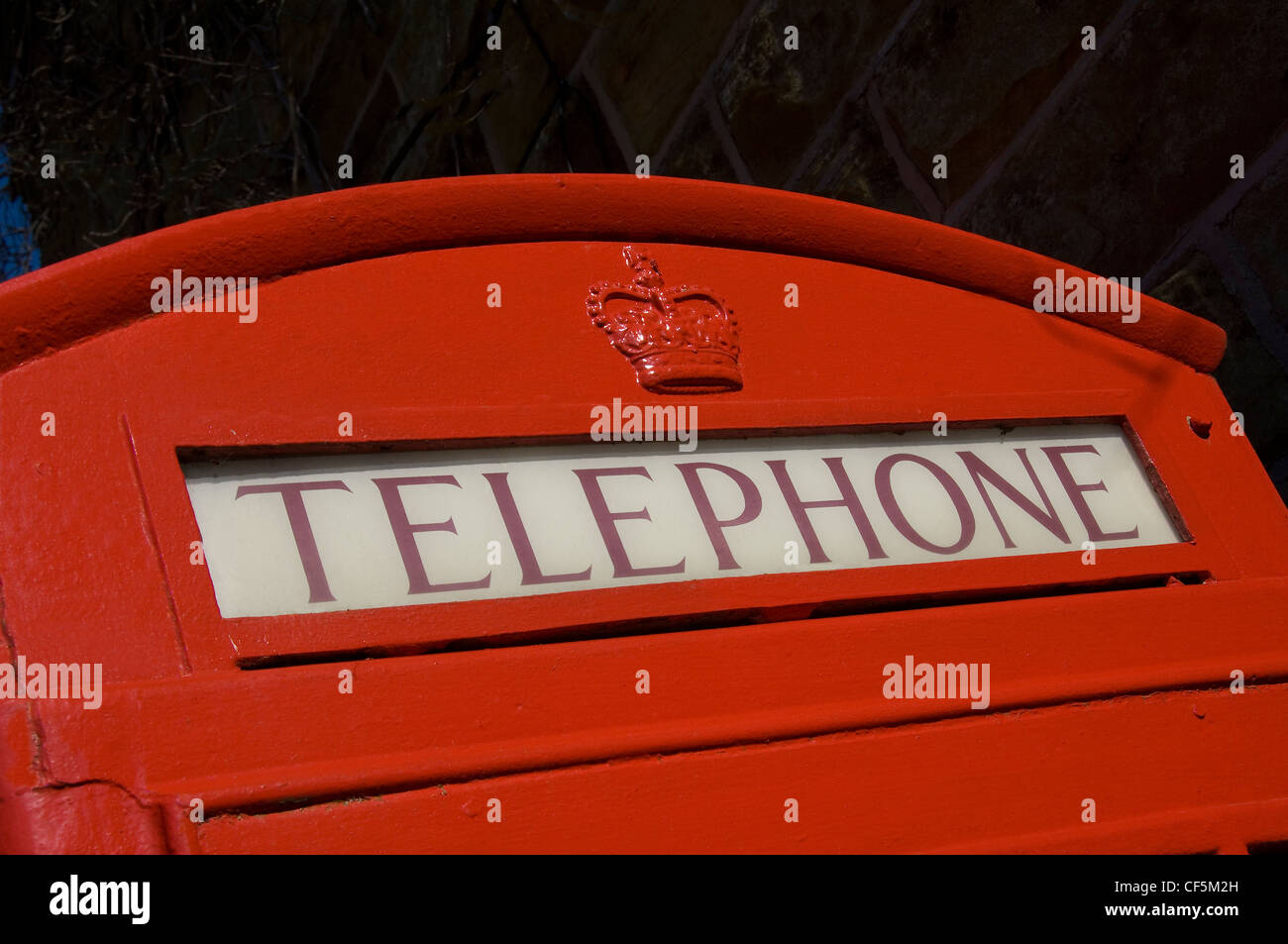The top of a traditional red telephone box. - Stock Image