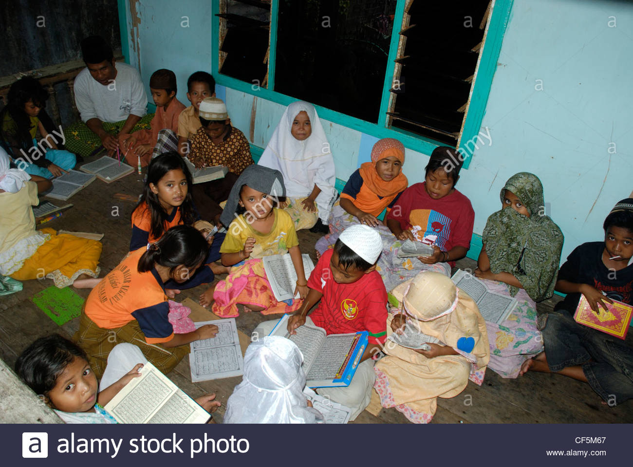A group of Muslim boys and girls aged 7 - 8 years old sitting on the floor learning to read the Koran in Arabic - Stock Image
