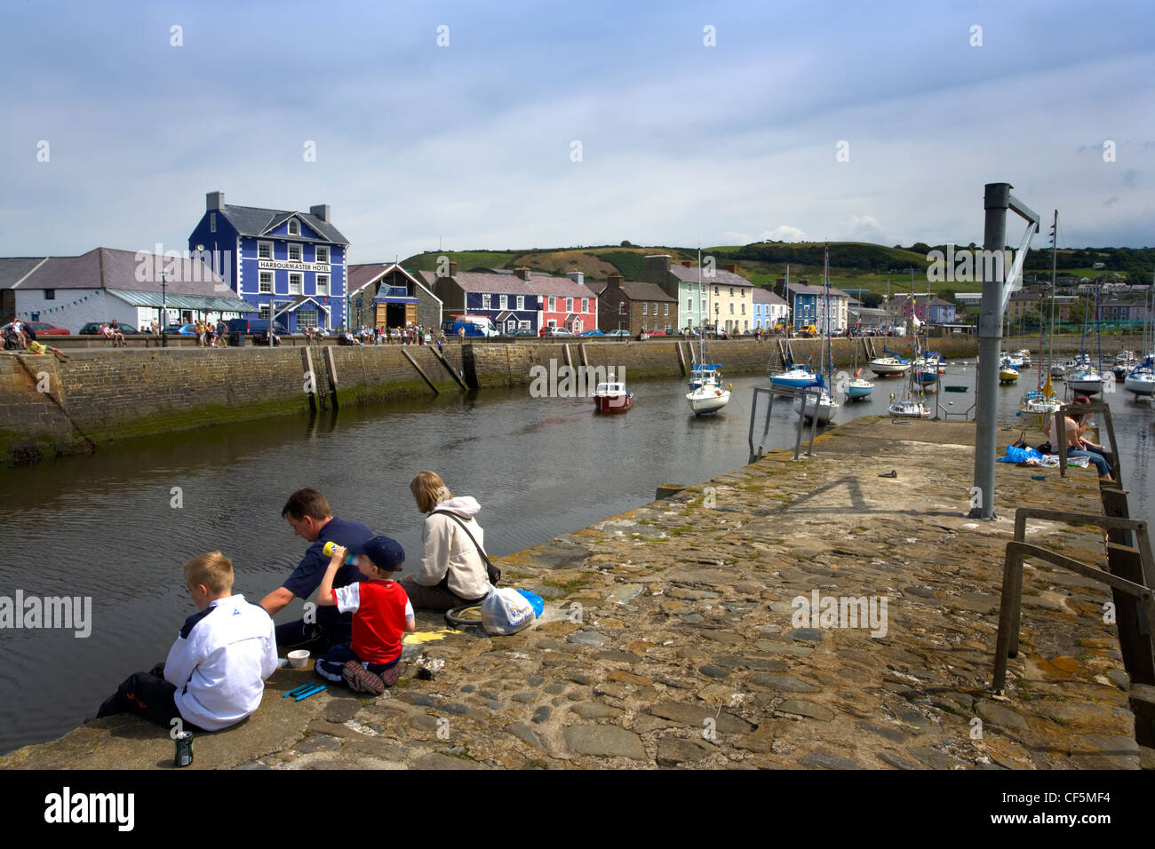 A family sitting on the quayside at Aberaeron. It is one of Wales' very first planned towns, the idea of establishing - Stock Image