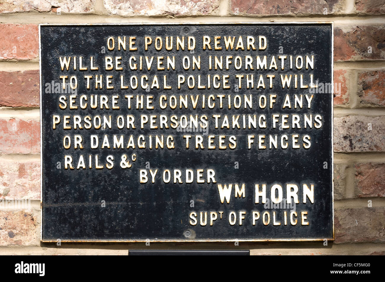 Railway sign offering a reward of one pound for information to secure a conviction for persons or person taking - Stock Image