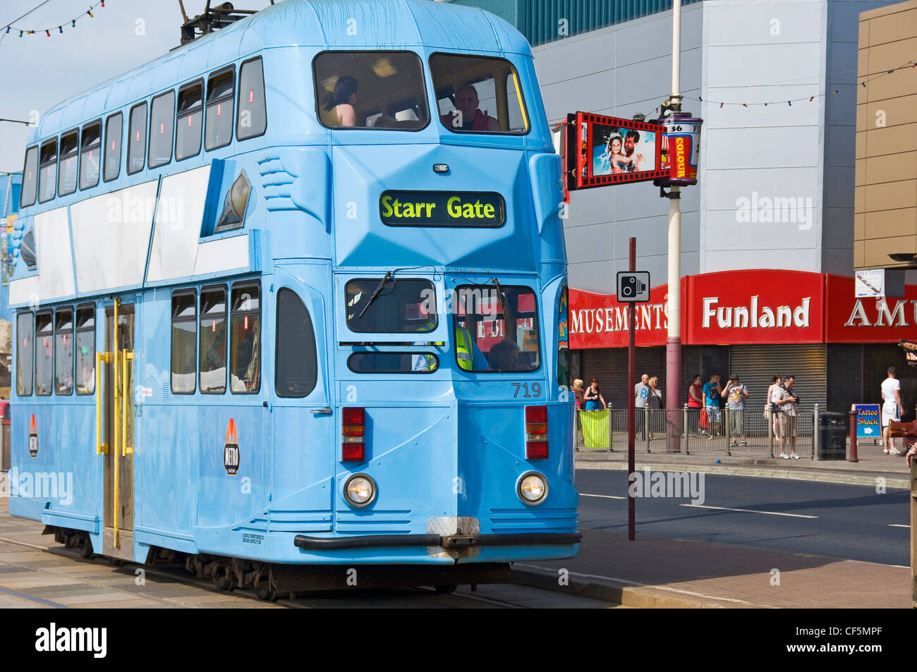 An electric tram travelling the Golden Mile in Blackpool. - Stock Image