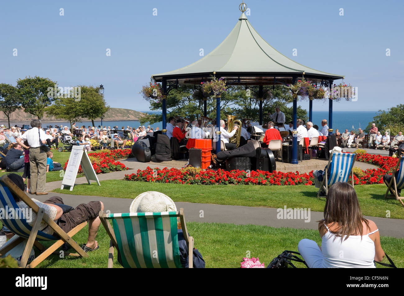 Holidaymakers listening to the brass band playing in the bandstand in Crescent Gardens. - Stock Image