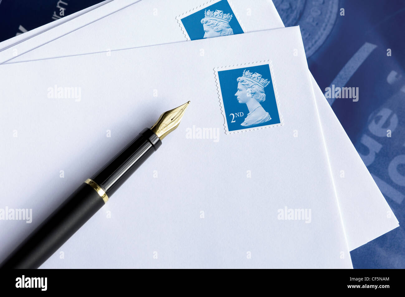 A still life featuring a fountain pen resting on white envelopes bearing second class British stamps. - Stock Image