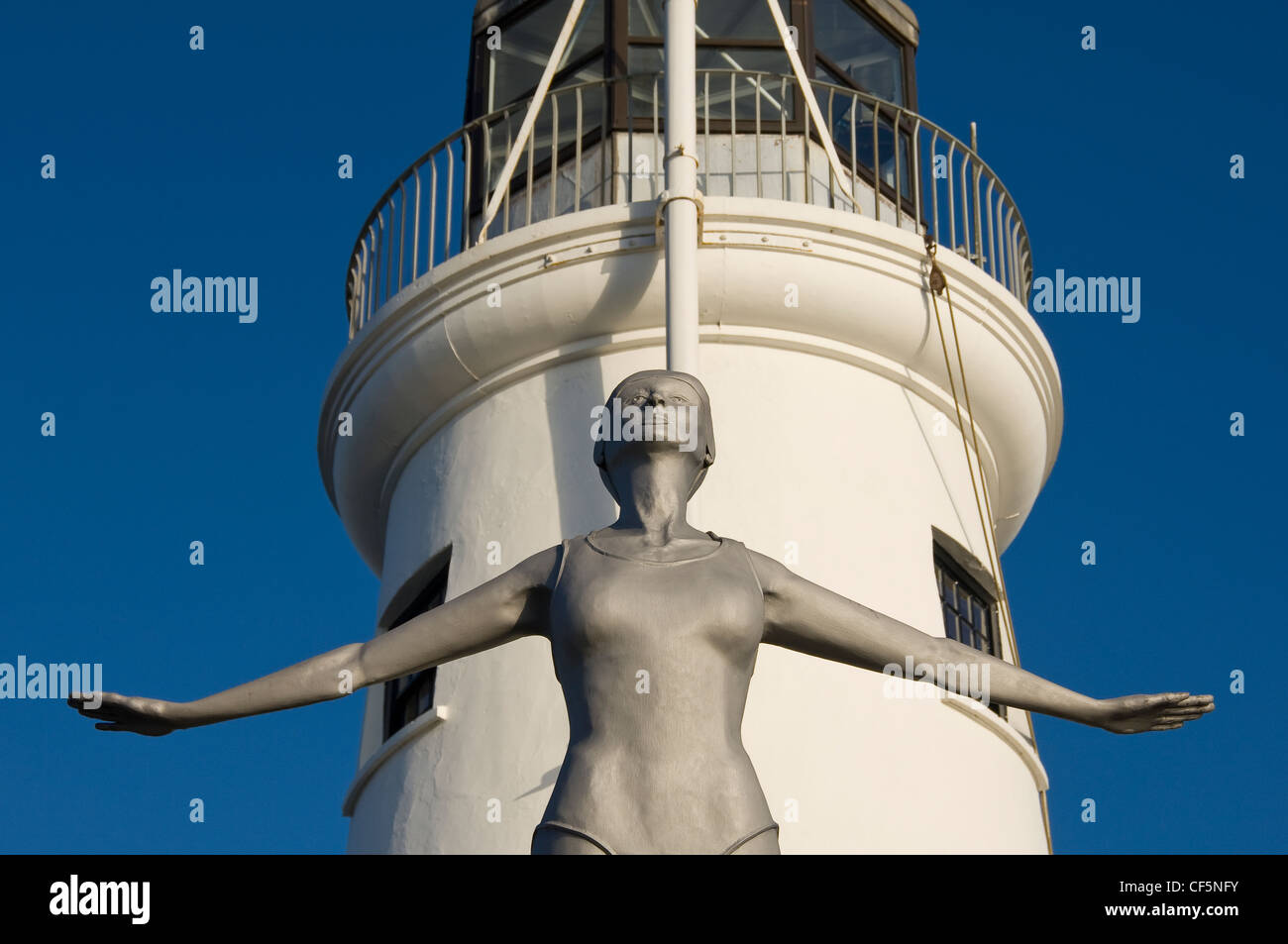 The Diving Belle sculpture representing Scarborough of the present by Craig Knowles next to Scarborough Lighthouse - Stock Image