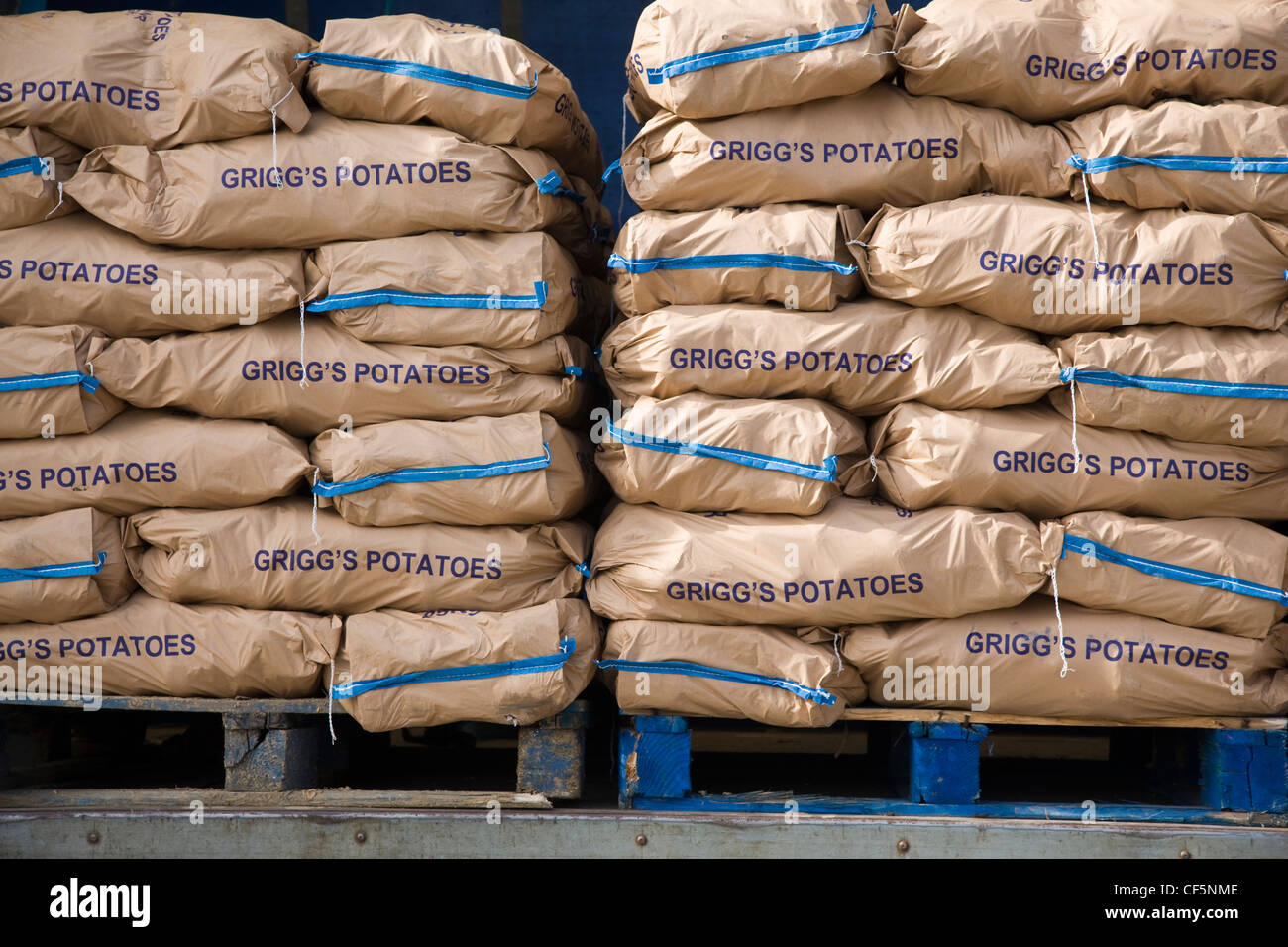 Sacks of Grigg's potatoes stacked on the back of a delivery lorry - Stock Image