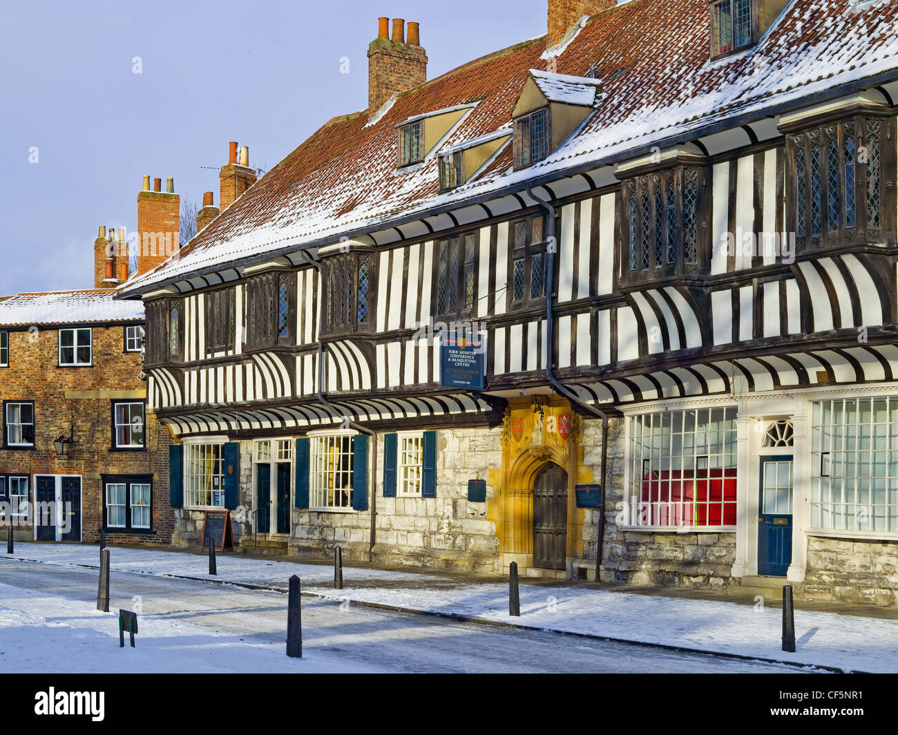 Snow covering the pavements and road by St Williams College close to York Minster. St. William's College was - Stock Image