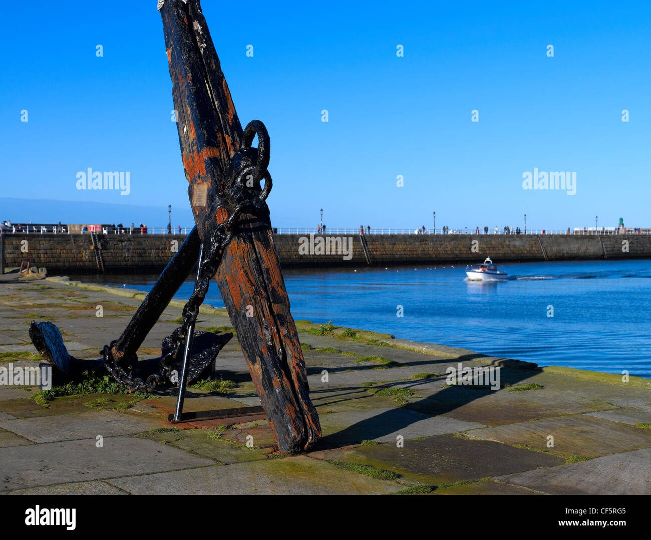 Old wooden stock anchor on the harbour quayside. - Stock Image