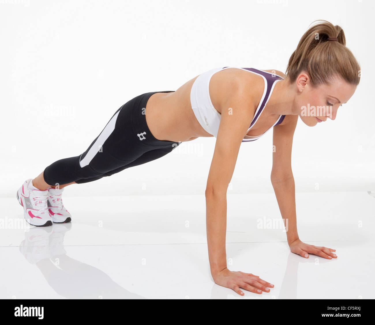 Upper body exercise Female fair hair tied into ponytail, wearing a cropped vest, black leggings and trainers, performing - Stock Image