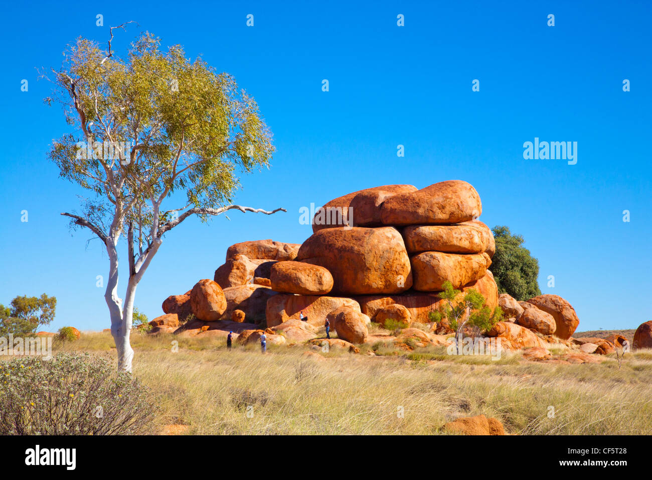 Devils Marbles, rock formations in the Northern Territory, Australia, with tourists clambering on them. - Stock Image