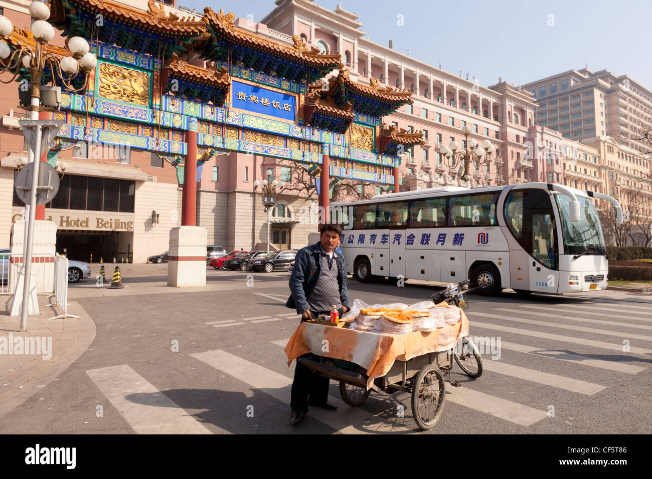 A street food vendor selling pizza outside the Grand Hotel, Chang'an Avenue, Beijing, China, tourist coach in - Stock Image