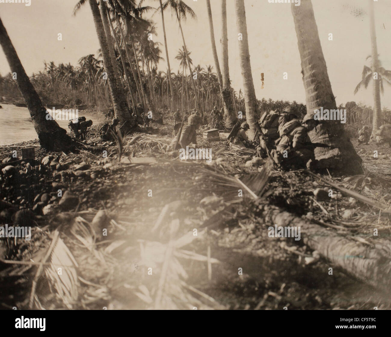 US Marine Corps WWII Pacific Campaign: Troops of 3rd wave 'A' Co 5th Marines consolidate position on beach. - Stock Image