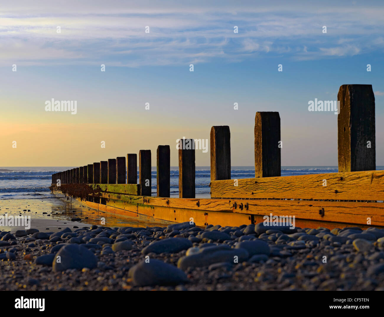 View along a groyne out to the Irish Sea on the beach at Borth at dusk. - Stock Image