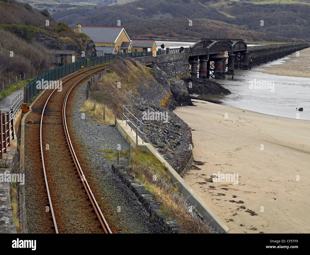 Barmouth Bridge, a single track railway over the estuary of the Afon Mawddach river at low tide. Stock Photo