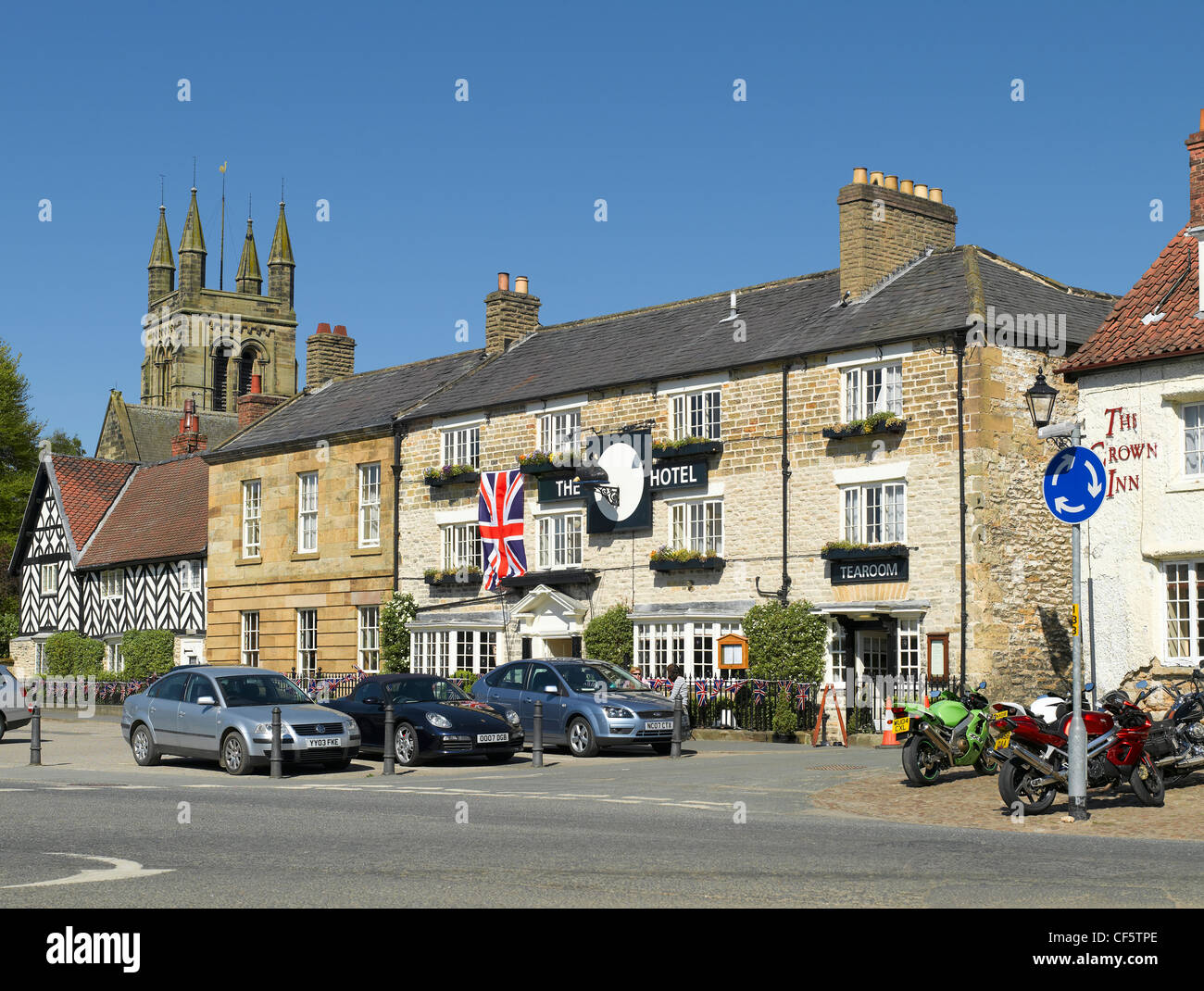 The Black Swan Hotel, a historic inn now a boutique hotel in Market Place. The tower of All Saints Church is in - Stock Image