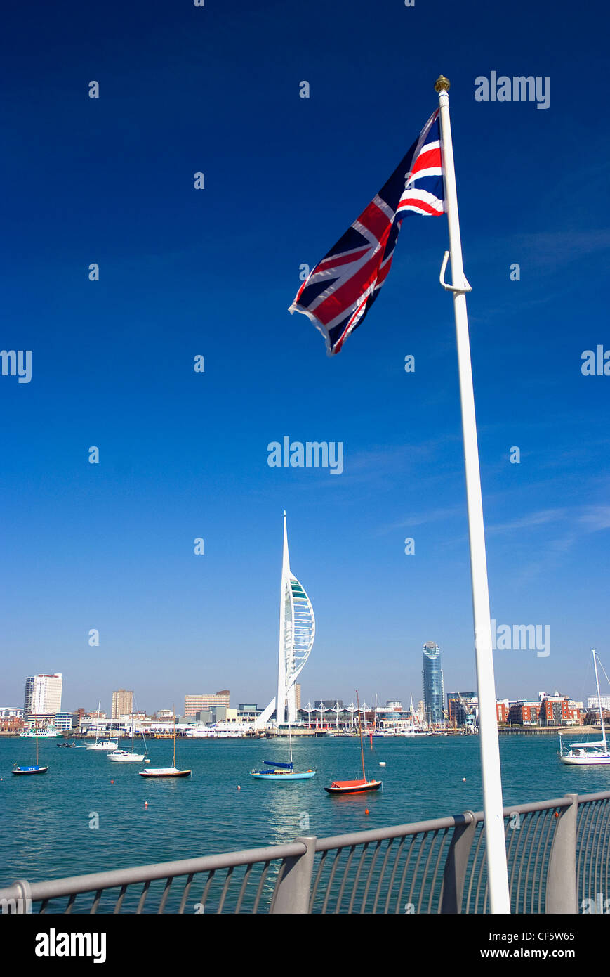A Union Jack flag flying on the waterfront at Gosport opposite the 170m high Spinnaker Tower at Gunwharf Quays in Stock Photo