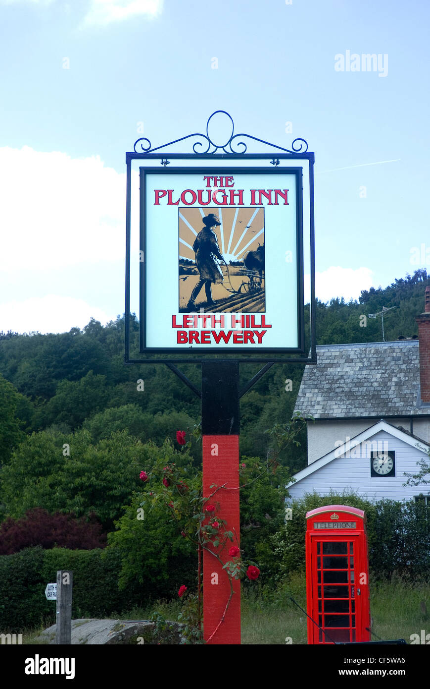 The Plough Inn pub sign and traditional red telephone box near Coldharbour. - Stock Image