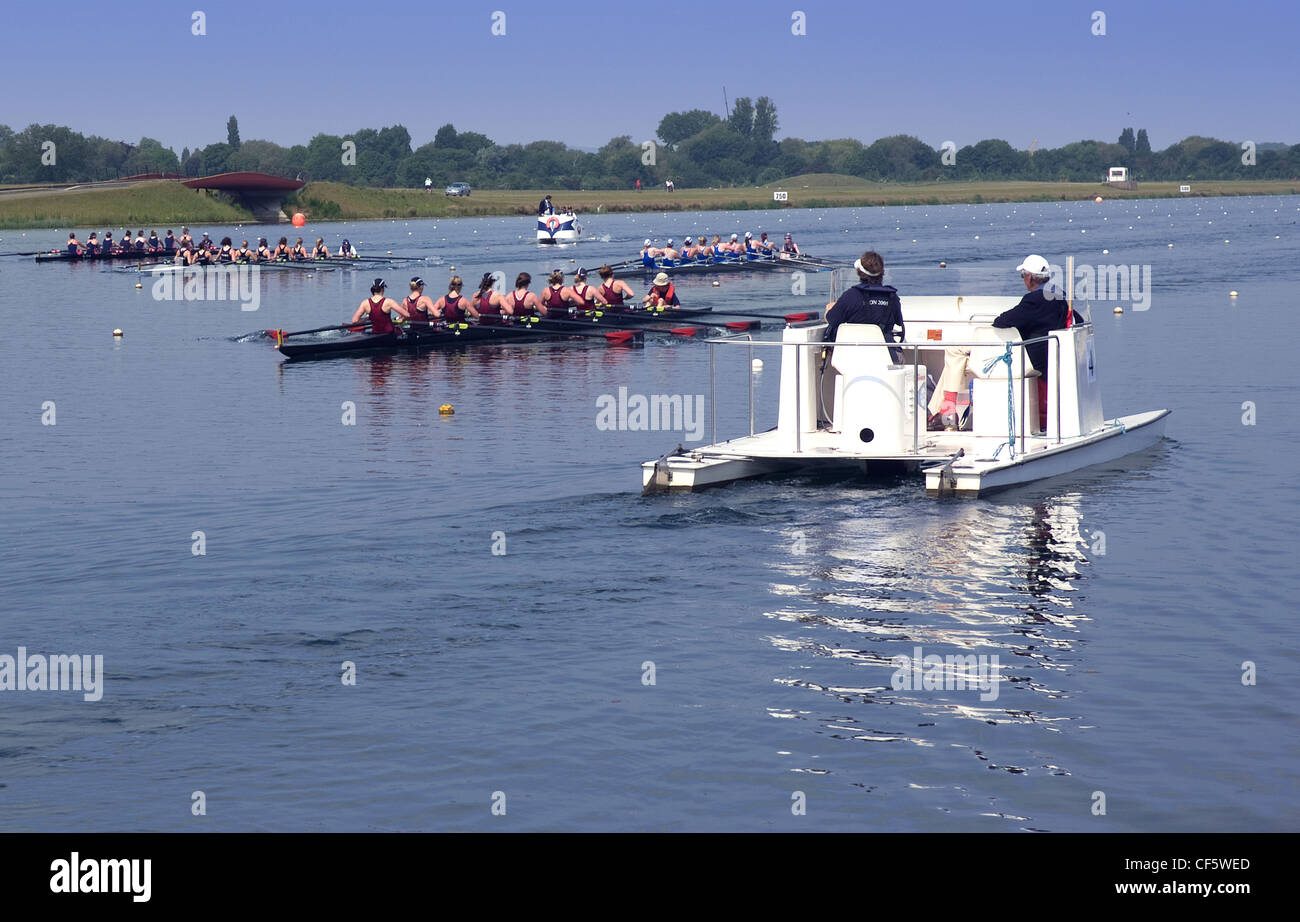 Crews of eight pass a referees boat in a a race at Eton Dorney, the venue for Rowing, Paralympic Rowing and Canoe - Stock Image