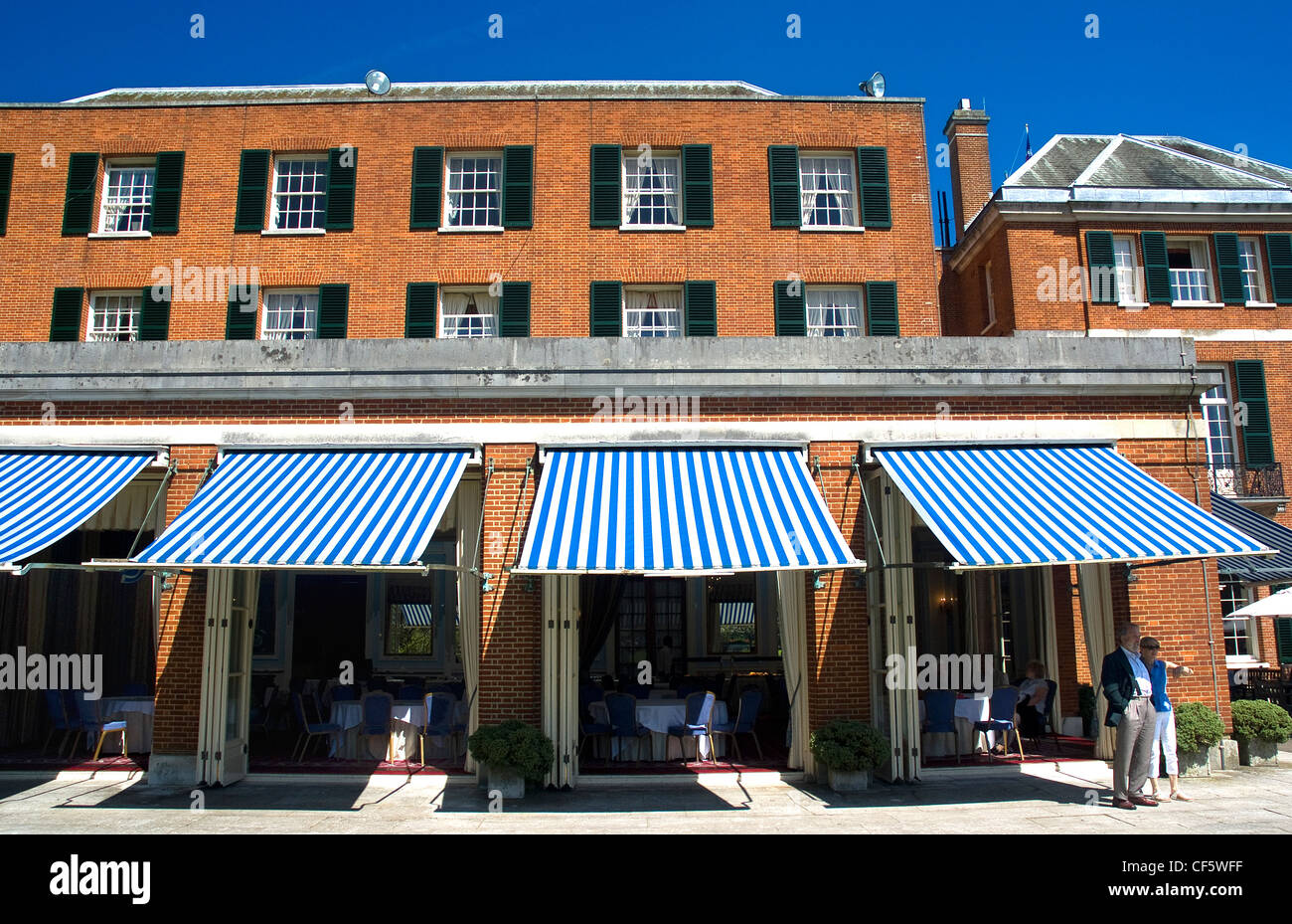 A couple standing on a terrace outside a restaurant at Woodcote Park, a private members club on the North downs - Stock Image