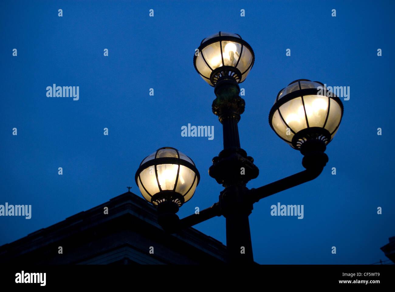 An illuminated street light outside the British Museum at night. - Stock Image