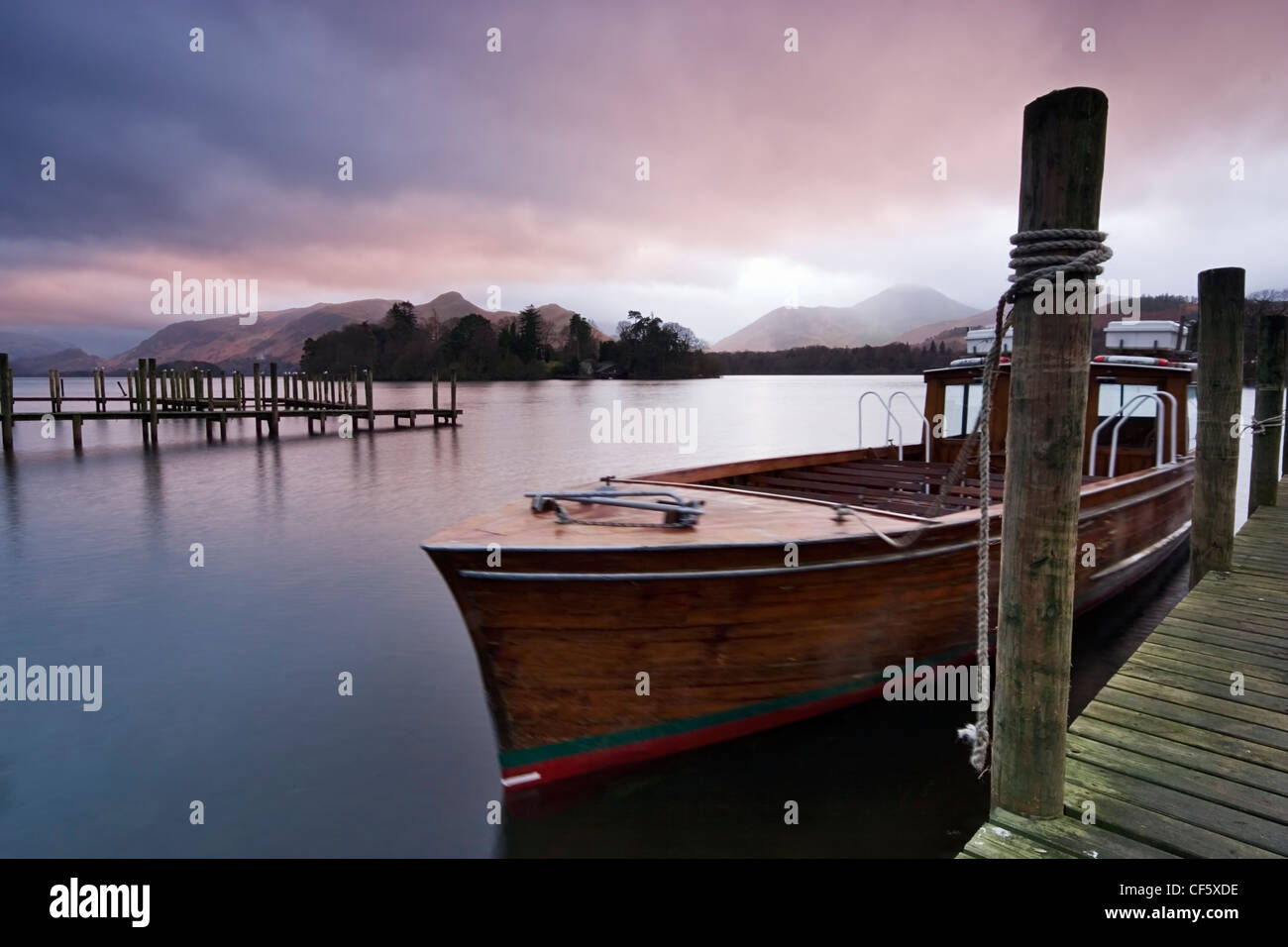 Boats tied up on the landing stage at Derwent Water. Watched over by the fells of Derwent, and Castlerigg, the lake - Stock Image