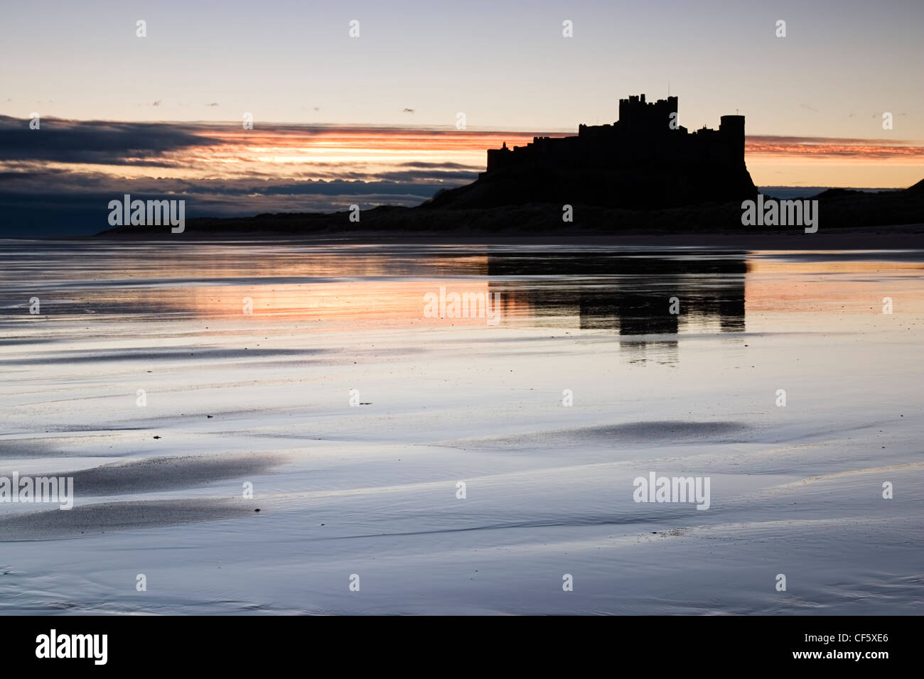 The outline of Bamburgh Castle against the sunrise. In the Wars of the Roses, Bamburgh was held by the Lancastrians - Stock Image