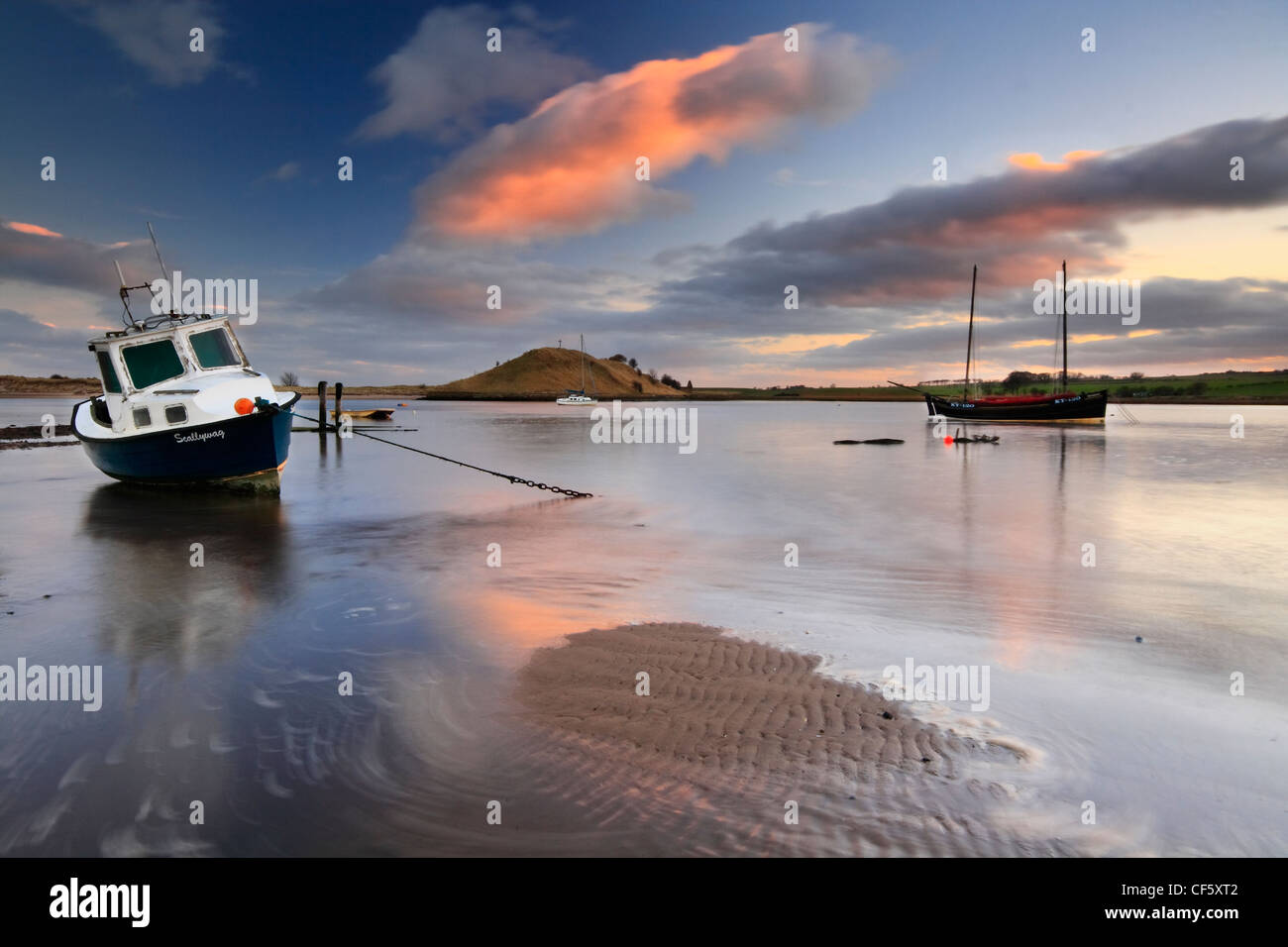An old fishing boat moored in Alnmouth estuary at low tide. Stock Photo