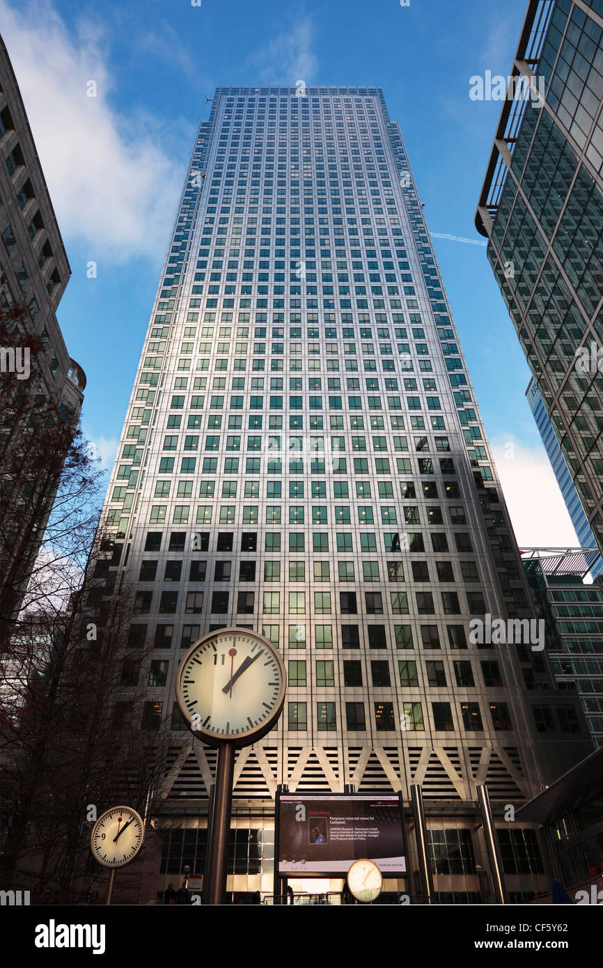 Looking up past clocks in Cabot Square to the Canary Wharf Tower (One Canada Square) the UK's tallest building. - Stock Image