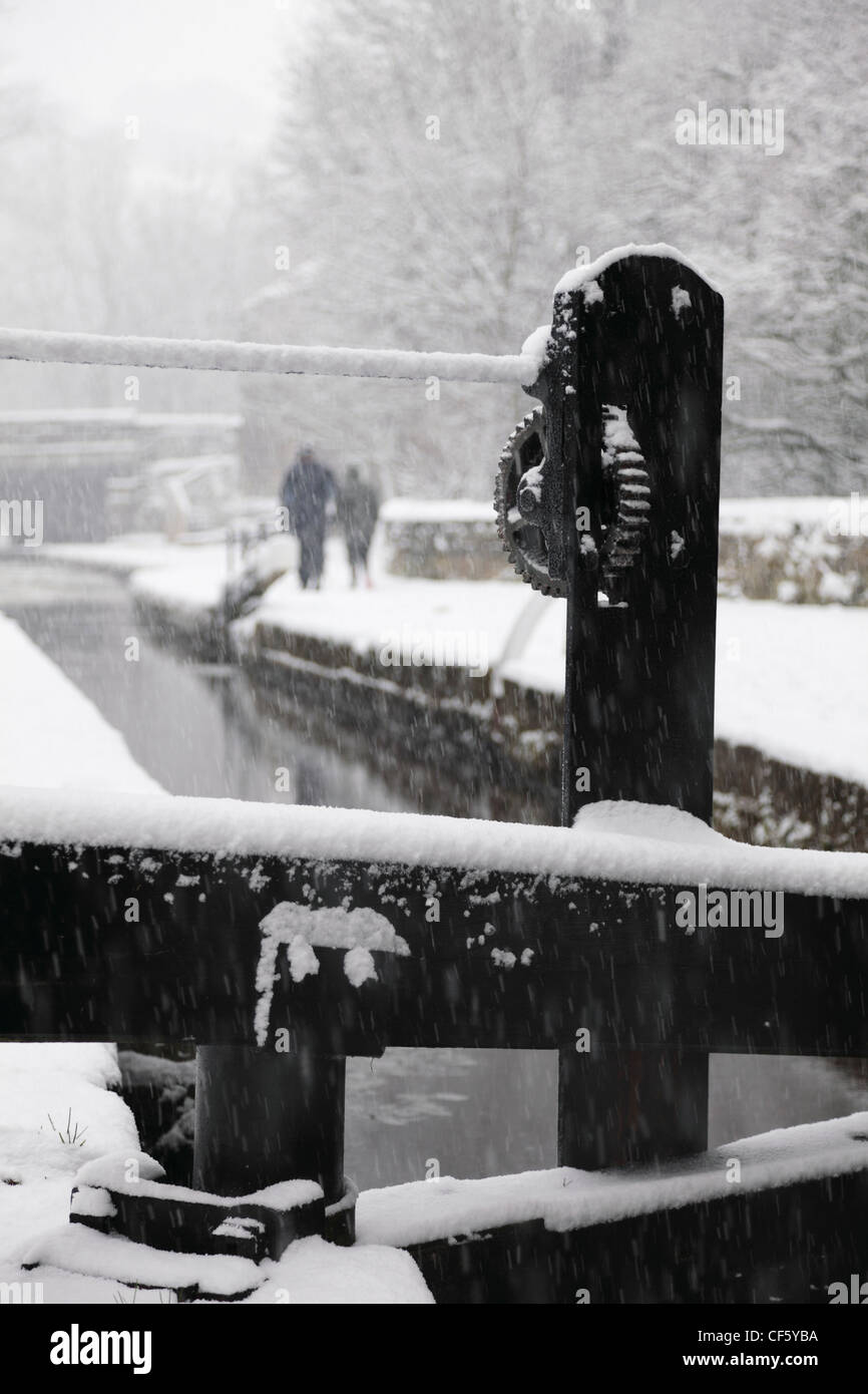 Two people walking along a towpath by the Huddersfield Narrow Canal in the snow. - Stock Image