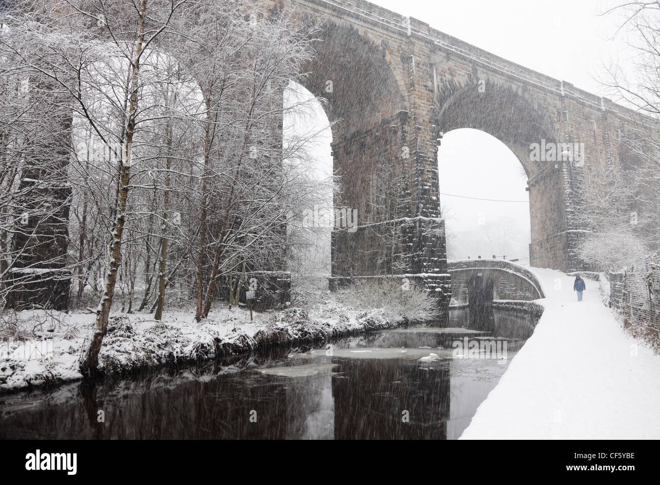 A woman walking along the towpath of the Huddersfield Narrow Canal beneath Saddleworth Viaduct in heavy snow. - Stock Image