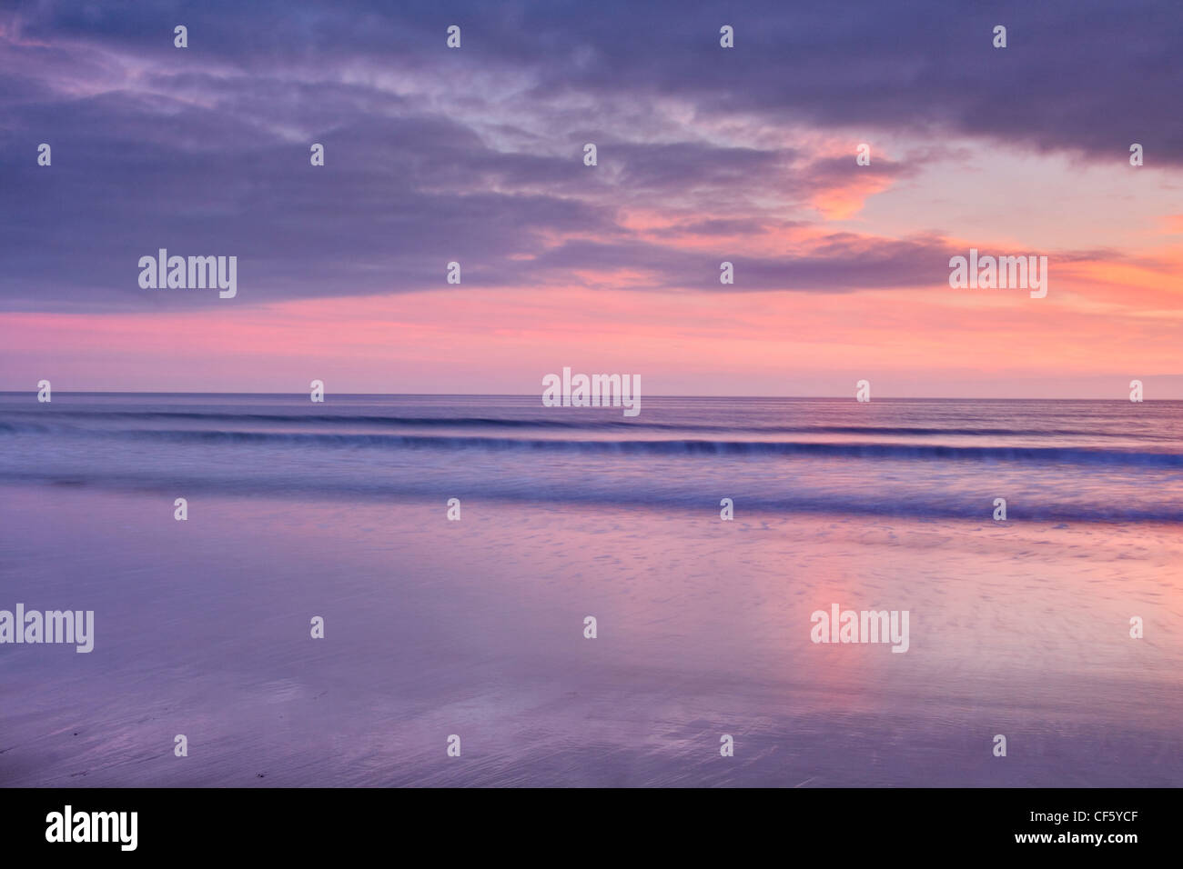 Waves rolling onto the beach below purple skies at sunset over Marloes Sands. - Stock Image