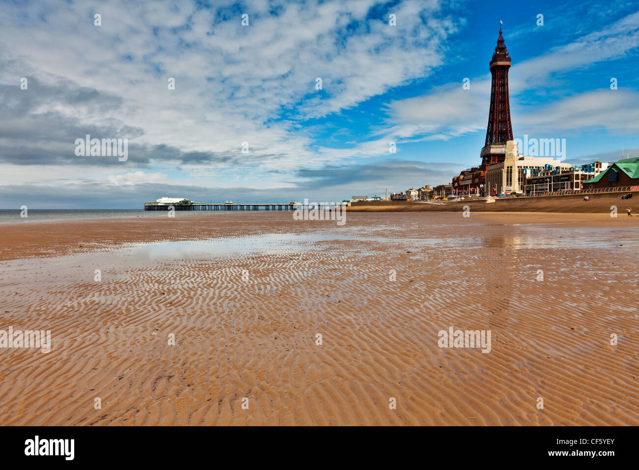 A view across the sandy beach towards Blackpool tower and North Pier on a summers day. - Stock Image