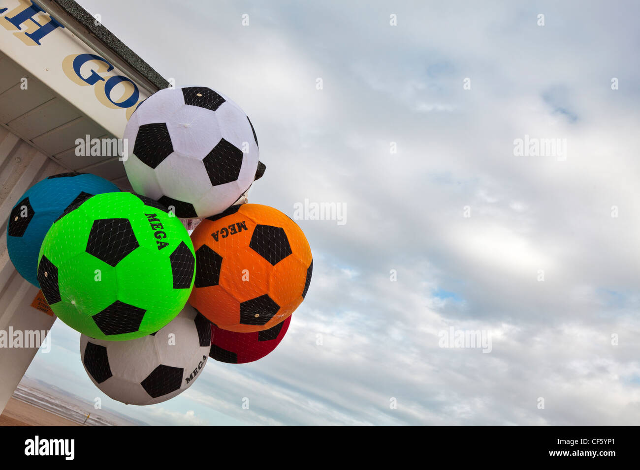 Soft foam footballs hanging outside a shop on the seafront at Weston-super-Mare on the Bristol Channel. Stock Photo